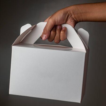 Kid holding a blank white cake box.