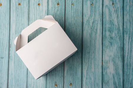 White Cardboard Fast Food Box, Packaging For Lunch on wooden table. Ready For Your business design.