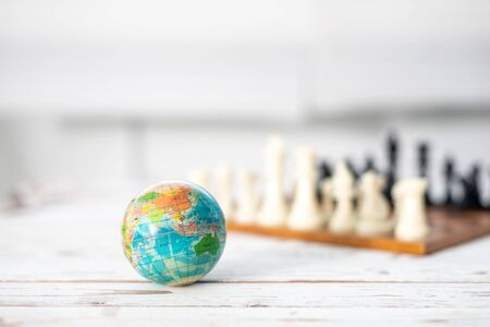 Travel The World. Chess pieces and world map globe. Shallow depth of field