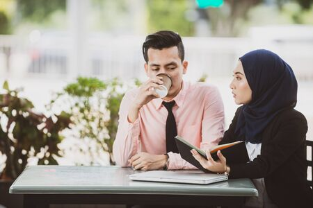Co-worker discussing over coffee break at a cafe. Malay Muslim couple