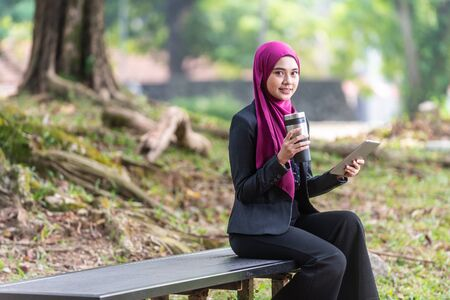 Muslim Businesswon on her table during a coffee break. Outdoor setting at a park. 版權商用圖片