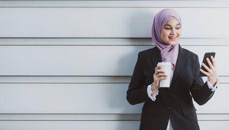 Trabajadora musulmana con su smartphone durante su pausa para el café. Foto de archivo