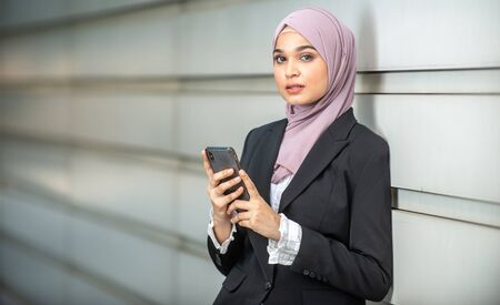 Young Female Muslim Entrepreneur looking at her smartphone. Shallow depth of field. Stock Photo