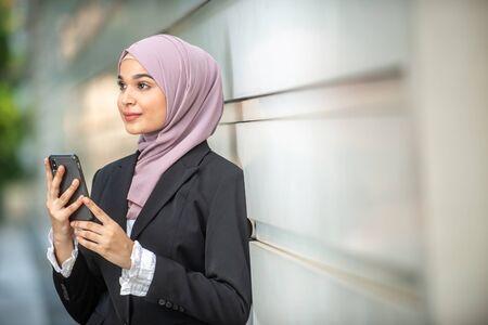 Jonge vrouwelijke moslimondernemer die naar haar smartphone kijkt. Ondiepe scherptediepte. Stockfoto