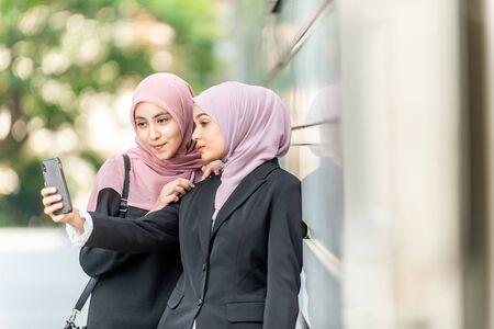 Asian Muslim girls taking a selfie. Outdoor setting.