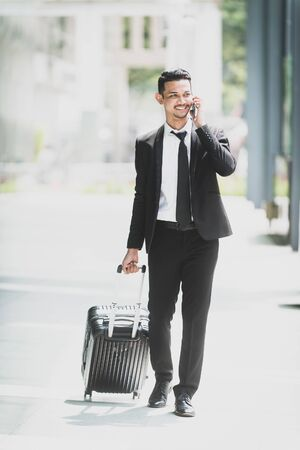 Young Travelling Businessman talking on his smartphone