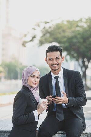 Muslimischer Geschäftsmann und Geschäftsfrau diskutieren über die Verwendung einer Smartphone-Verbindung für die Arbeit. Outdoor-Einstellung. Standard-Bild