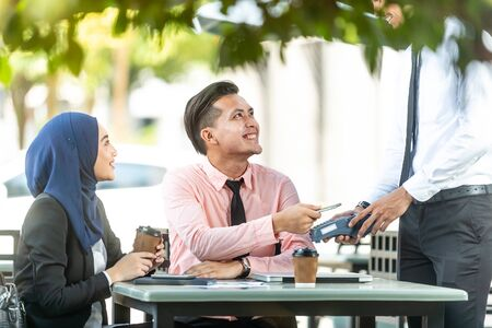 Waiter interacting with Muslim customers using bank terminal to process and acquire mobile payment at a coffee shop on a sunny day. Modern cafe start up small business micropayment concept. Banque d'images