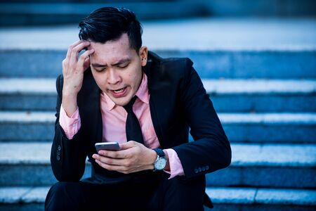 Stressed and angry asian businessman  looking at smartphone screen with irritation. Annoyed male received bad news, device gadget broken or dead concept