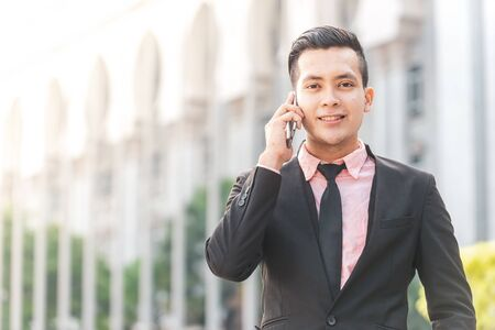 Young Malay Business Man on his Smartphone.