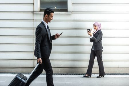 Muslim Business People on their Smartphone while on a coffee break, walking towards each other. Shallow depth of field.