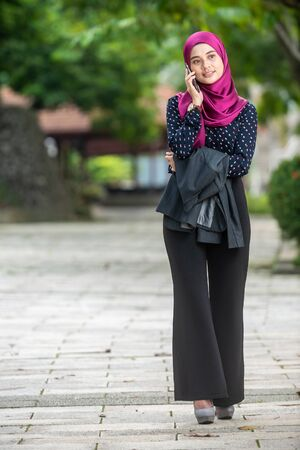 Muslim Businesswoman Talking on her smartphone at a park. Negative Space for text.