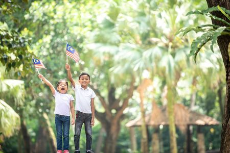 Boy and Girl with Malaysia Flag. Independence Day concept. Outdoor Setting Imagens - 129958373