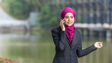 Muslim Corporate Lady talking on her smartphone. Outdoor Setting. Negative Space for text 版權商用圖片