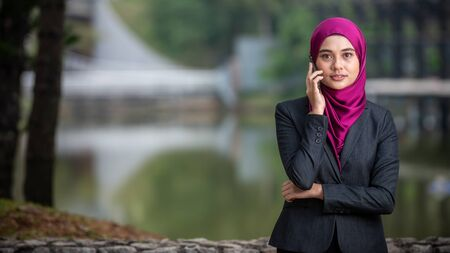 Muslim Corporate Lady talking on her smartphone. Outdoor Setting. Negative Space for text