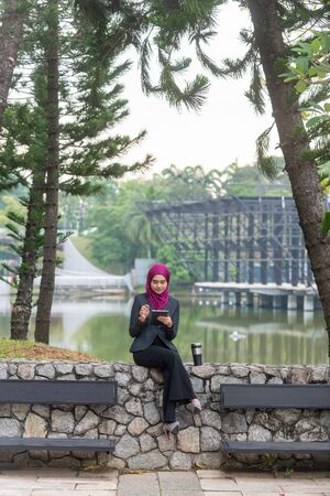 Muslim Businesswoman with her tablet and her coffee at the park.
