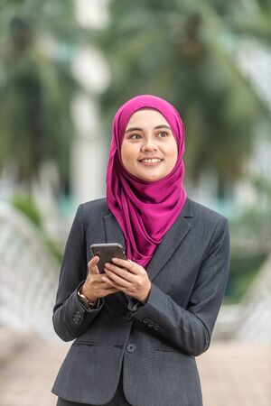 Beautiful Muslim Businesswoman with her Smartphone. Technology and communication concept. 版權商用圖片