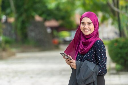Moslimvrouw met haar smartphone. Buitenomgeving
