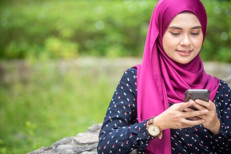 Muslim Woman with her smartphone. Outdoor Setting