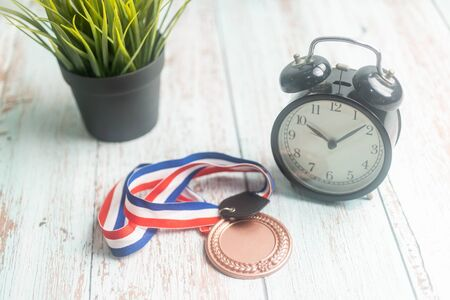 Sport Medal and alarm clock on wooden background. Winning Time concept Фото со стока