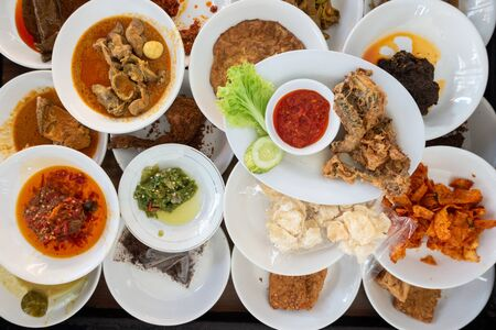 "The famous ""Nasi Padang"" in Indonesia. Rice is served with many dishes like chicken, beef, mix vegetables and eggs."