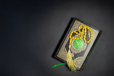 Islamic Concept - Holy Quran on Black Background. Shallow depth of field Stock Photo