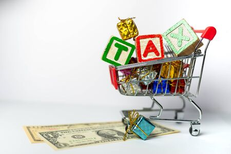 Sales Tax Concept - US Dollars, Shopping cart, Calculator on white background. Shallow depth of field.