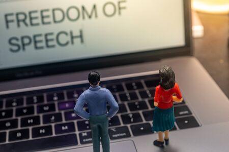 Concepto de libertad de expresión: personas en miniatura mirando una computadora portátil. Poca profundidad de campo.