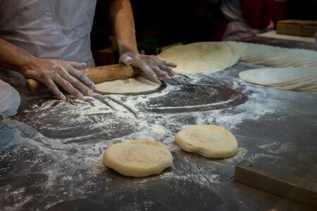 Blurry Baker's Hands pétrissage de la pâte dans une boulangerie. Mise au point douce, faible profondeur de champ, mouvement flou.