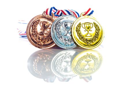 Medals - gold, silver and bronze isolated on white. Reflected. Shallow depth of field Standard-Bild