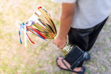 Kid holding a trophy. He is a winner