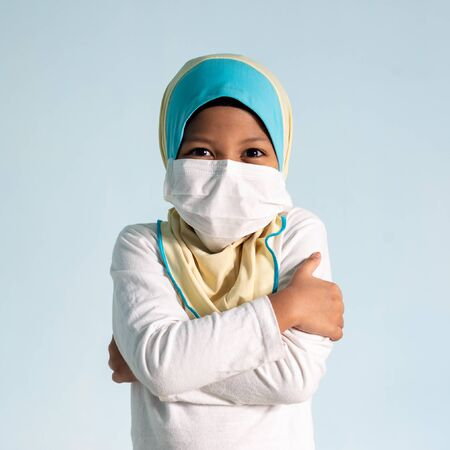 Muslim girl with hijab wearing surgical mask. Covid-19 and coronavirus concept. Shallow depth of field