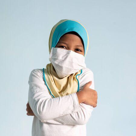 Muslim girl with hijab wearing surgical mask. Covid-19 and coronavirus concept. Shallow depth of field Zdjęcie Seryjne - 143119413