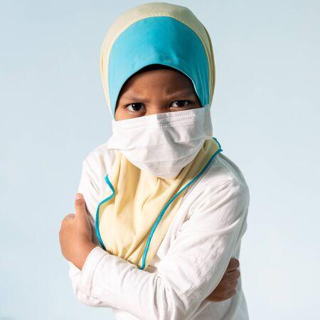 Muslim girl with hijab wearing surgical mask. Covid-19 and coronavirus concept. Shallow depth of field Zdjęcie Seryjne - 143119438