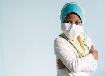 Muslim girl with hijab wearing surgical mask. Covid-19 and coronavirus concept. Shallow depth of field Zdjęcie Seryjne - 143119442