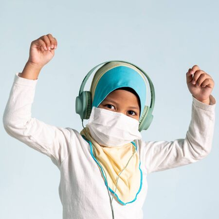 Muslim girl with hijab wearing surgical mask listening to music on her headphone. Covid-19 and coronavirus concept. Shallow depth of field Zdjęcie Seryjne - 143119451