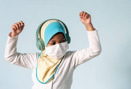 Muslim girl with hijab wearing surgical mask listening to music on her headphone. Covid-19 and coronavirus concept. Shallow depth of field Zdjęcie Seryjne - 143119491