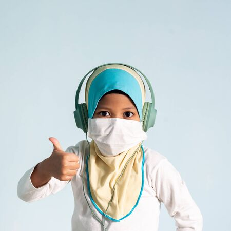 Muslim girl with hijab wearing surgical mask listening to music on her headphone. Covid-19 and coronavirus concept. Shallow depth of field Zdjęcie Seryjne - 143119512