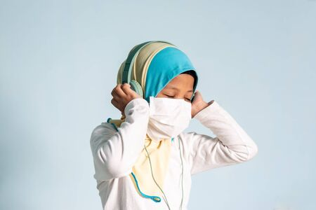 Muslim girl with hijab wearing surgical mask listening to music on her headphone. Covid-19 and coronavirus concept. Shallow depth of field