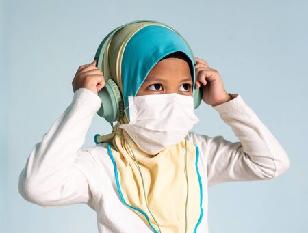 Muslim girl with hijab wearing surgical mask listening to music on her headphone. Covid-19 and coronavirus concept. Shallow depth of field Zdjęcie Seryjne - 143119591