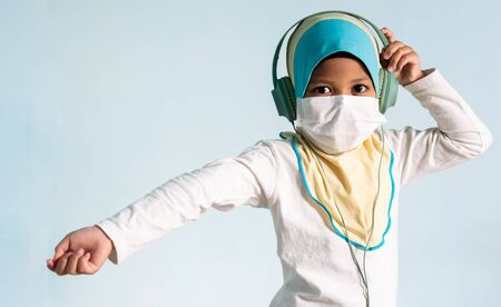 Muslim girl with hijab wearing surgical mask listening to music on her headphone. Covid-19 and coronavirus concept. Shallow depth of field Zdjęcie Seryjne - 143119614