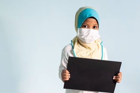 Muslim girl with hijab wearing surgical mask. Covid-19 and coronavirus concept. Shallow depth of field Zdjęcie Seryjne - 143119916