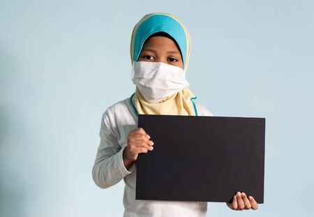 Muslim girl with hijab wearing surgical mask. Covid-19 and coronavirus concept. Shallow depth of field Zdjęcie Seryjne - 143119919