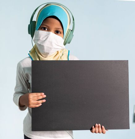 Muslim girl with hijab wearing surgical mask. Covid-19 and coronavirus concept. Shallow depth of field Zdjęcie Seryjne - 143119921