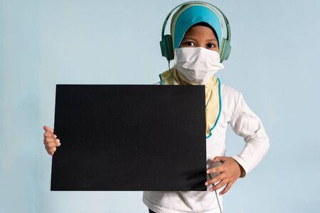 Muslim girl with hijab wearing surgical mask. Covid-19 and coronavirus concept. Shallow depth of field Zdjęcie Seryjne - 143119936