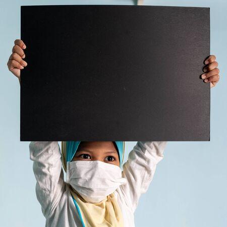 Muslim girl with hijab wearing surgical mask. Covid-19 and coronavirus concept. Shallow depth of field Zdjęcie Seryjne - 143119922