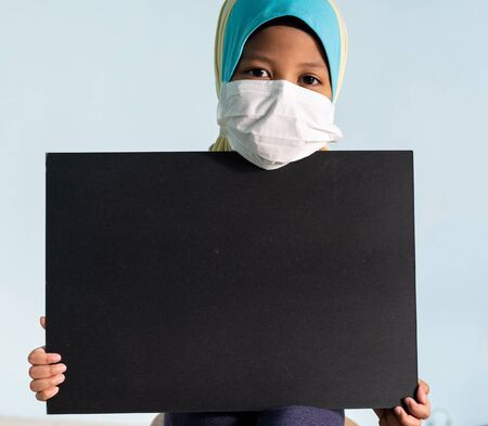 Muslim girl with hijab wearing surgical mask. Covid-19 and coronavirus concept. Shallow depth of field Zdjęcie Seryjne - 143119942