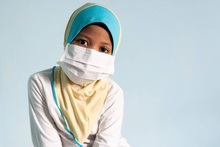 Muslim girl with hijab wearing surgical mask. Covid-19 and coronavirus concept. Shallow depth of field Zdjęcie Seryjne - 143119930