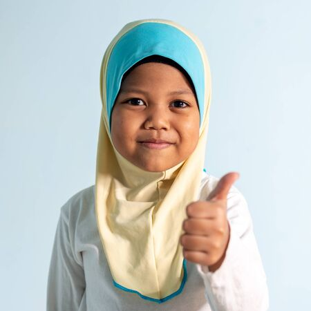 Thumbs up and  Happy Muslim girl wearing hijab isolated portrait.  Shallow depth of field