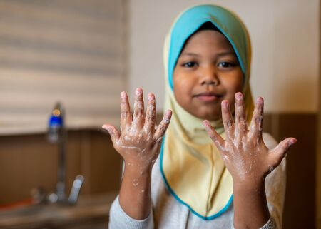 Muslim Girl washing hand in the kitchen. Cleanliness, covid-19, coronavirus concept. Shallow depth of field Reklamní fotografie